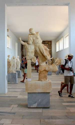 DELOS, GREECE - SEPTEMBER 15, 2016: Tourists visit the Archaeological site, marble statues in the Museum